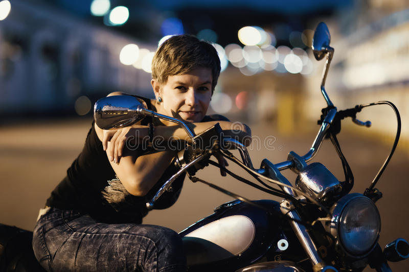Cute young brunette woman and motorcycle on street of Odessa stock image