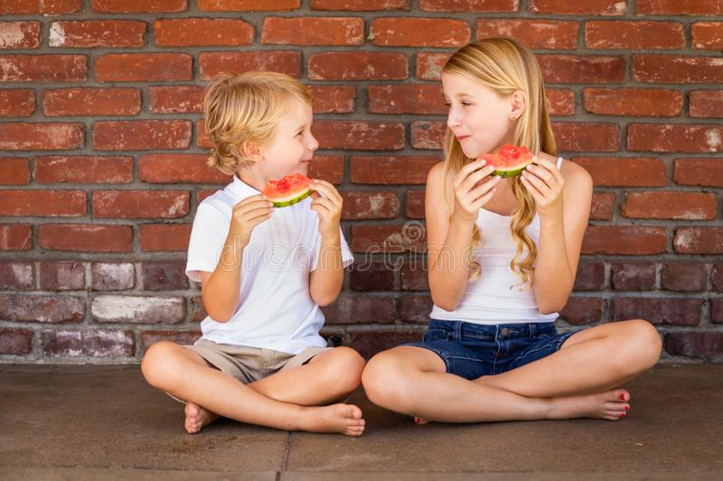 Cute Young Caucasian Boy and Girl Eating Watermelon Against Brick Wall royalty free stock images