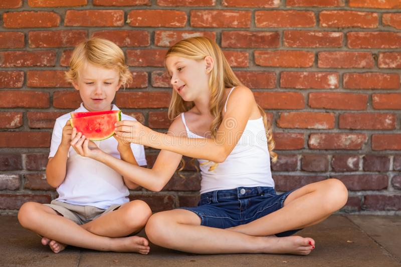Cute Young Caucasian Boy and Girl Share Watermelon Against Brick Wall stock photos