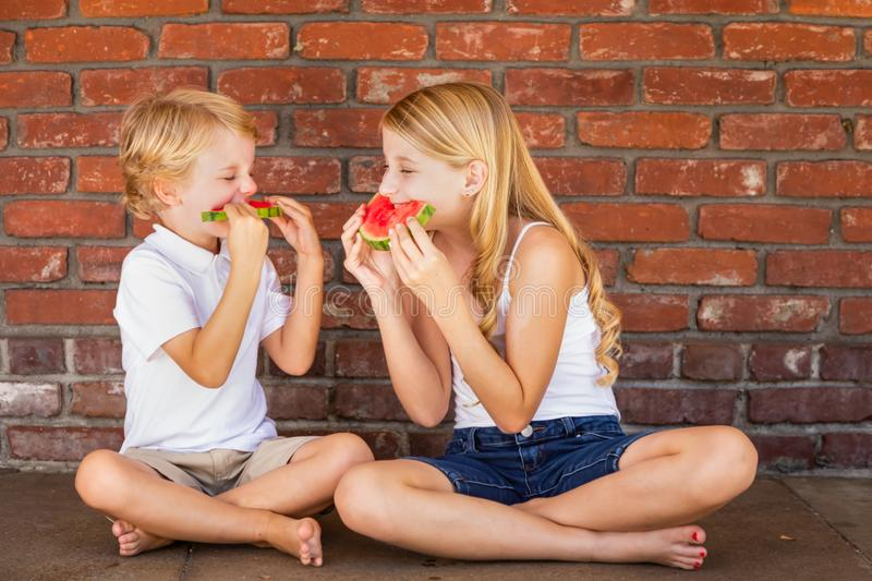 Cute Young Caucasian Boy and Girl Share Watermelon Against Brick Wall royalty free stock photo