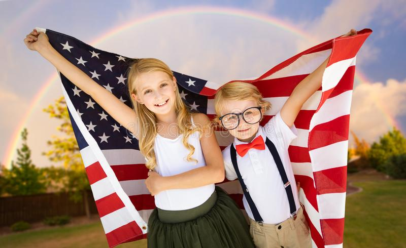 Cute Young Caucasian Boy and Girl Holding American Flag With Rainbow Behind stock photo