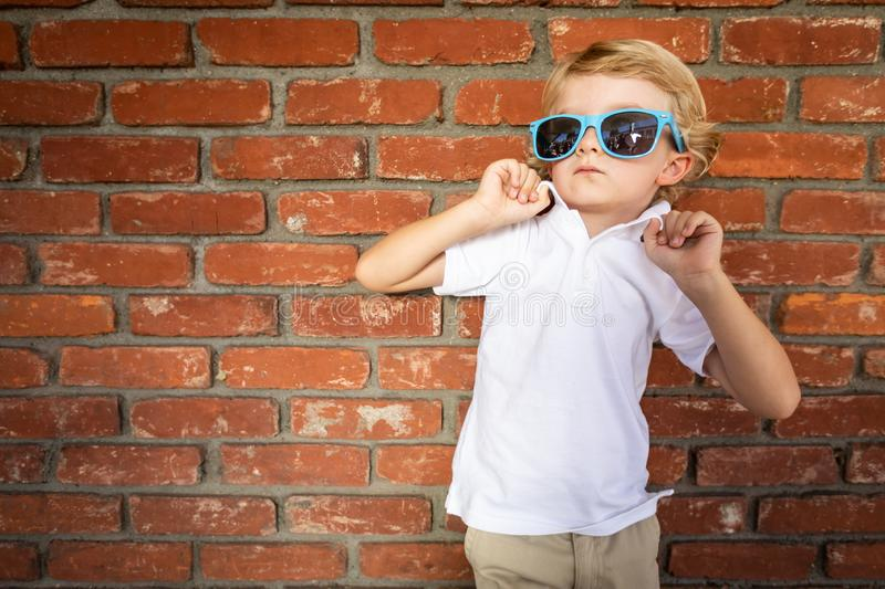 Cute Young Caucasian Boy Wearing Sunglasses Against Brick Wall royalty free stock photos