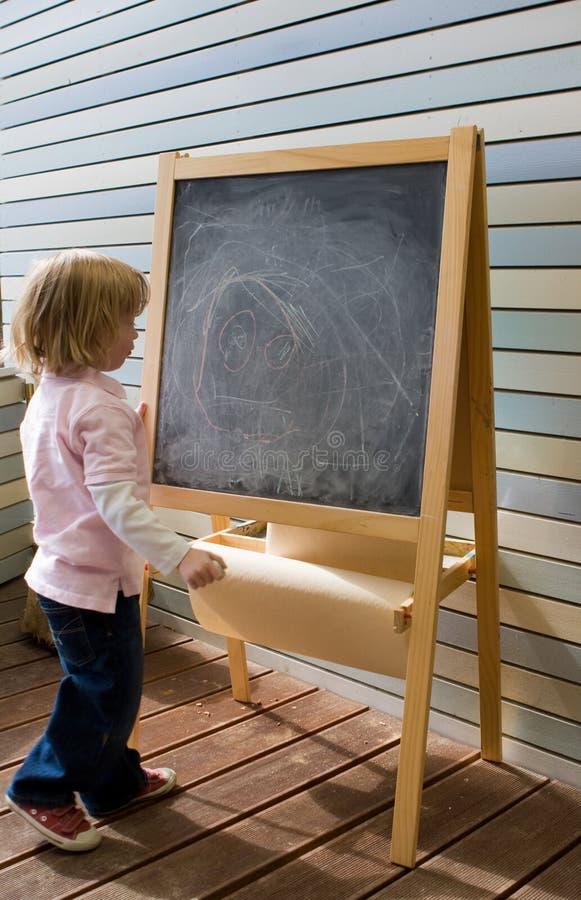 Download Cute Young Caucasian Boy Writing On A Blackboard Stock Photo - Image: 9509596