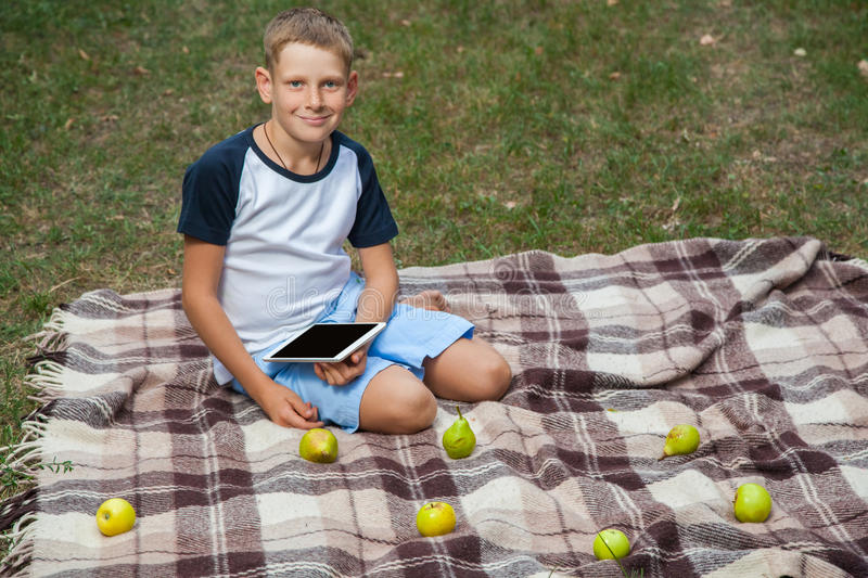 Cute young caucasian kid with freckles on his face in blue shorts and white and blue T-shirt holding tablet, siting on plaid, look. Ing at camera in park and stock image