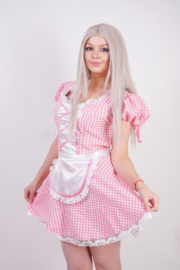 Cute young caucasian teen girl in pink plaid Bavarian dress with apron posing on white Studio solid background royalty free stock photo