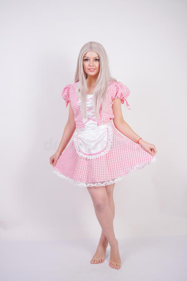Cute young caucasian teen girl in pink plaid Bavarian dress with apron posing on white Studio solid background royalty free stock photos