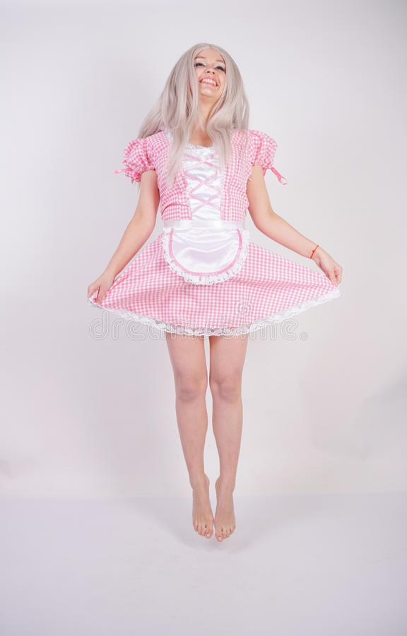 Cute young caucasian teen girl in pink plaid Bavarian dress with apron posing on white Studio solid background royalty free stock photography