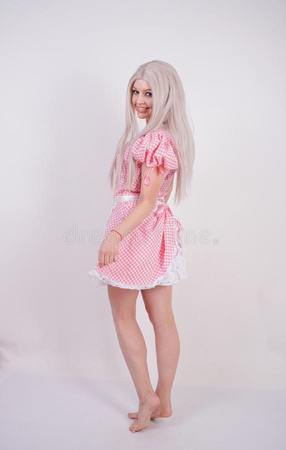 Cute young caucasian teen girl in pink plaid Bavarian dress with apron posing on white Studio solid background stock image