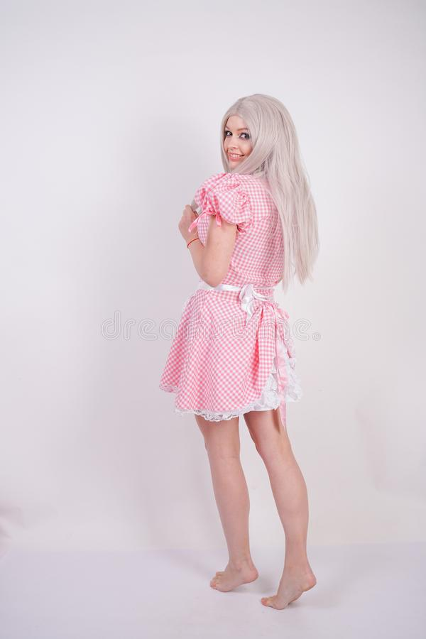 Cute young caucasian teen girl in pink plaid Bavarian dress with apron posing on white Studio solid background royalty free stock images
