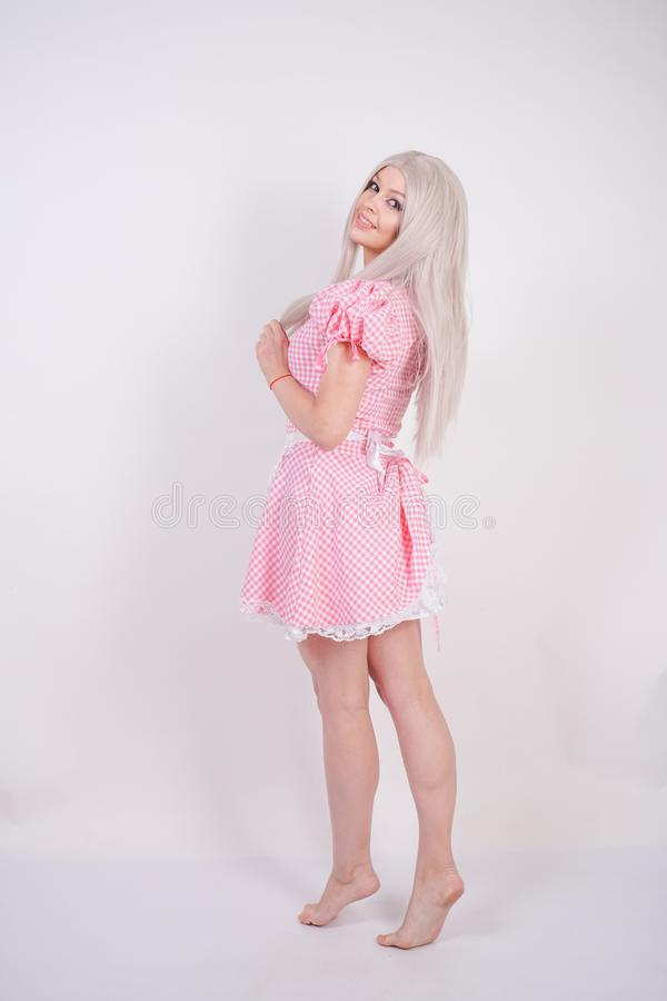 Cute young caucasian teen girl in pink plaid Bavarian dress with apron posing on white Studio solid background stock photos