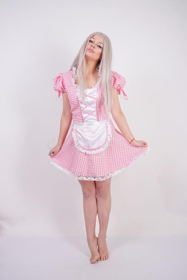 Cute young caucasian teen girl in pink plaid Bavarian dress with apron posing on white Studio solid background stock photo