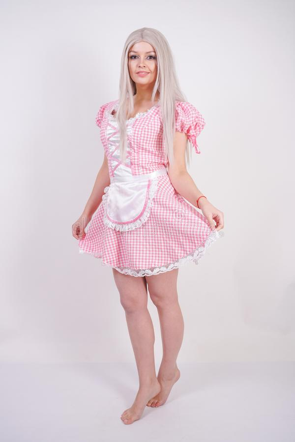 Cute young caucasian teen girl in pink plaid Bavarian dress with apron posing on white Studio solid background royalty free stock image