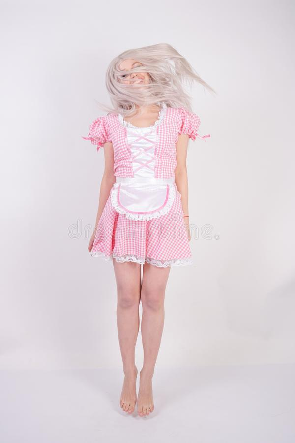Cute young caucasian teen girl in pink plaid Bavarian dress with apron posing on white Studio solid background stock photography