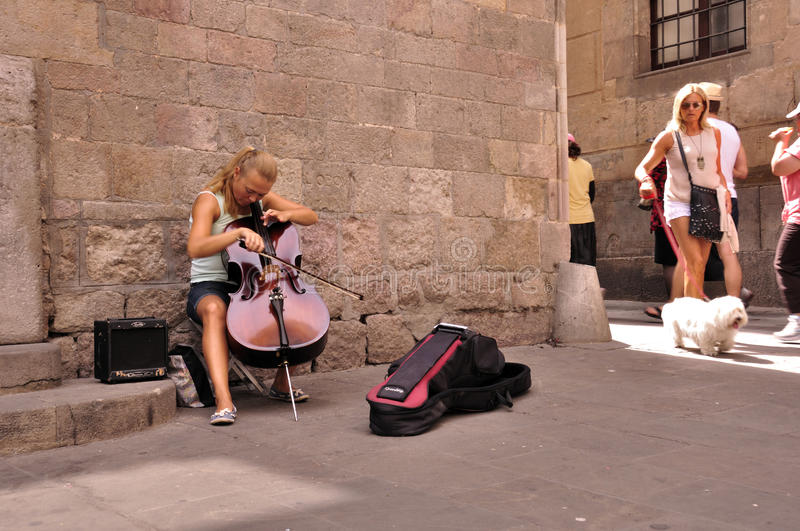 Cute young cellist street musician. In Barcelona, August 2012 royalty free stock photography