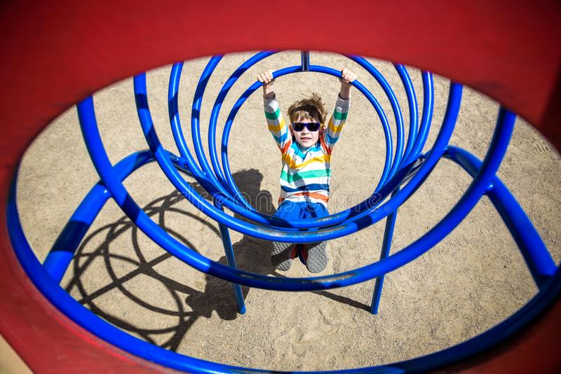 Cute young child boy or kid playing in tunnel on playground stock images