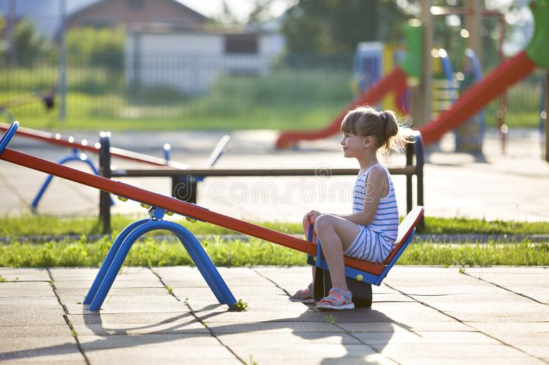 Cute young child girl outdoors on see-saw swing on sunny summer day stock photo