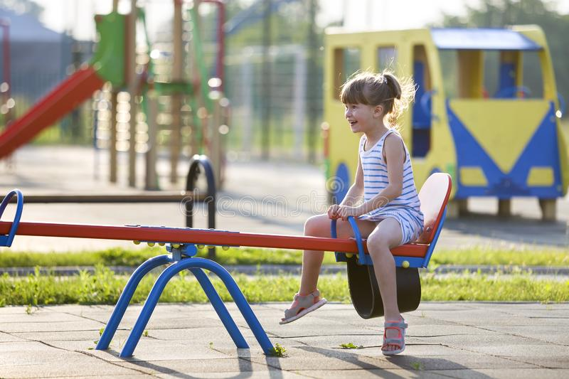 Cute young child girl outdoors on see-saw swing on sunny summer day stock image