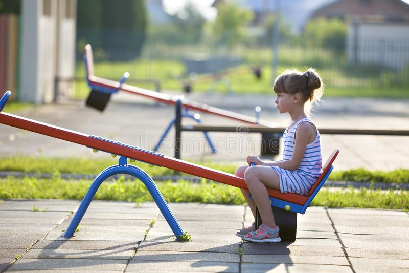 Cute young child girl outdoors on see-saw swing on sunny summer day royalty free stock images