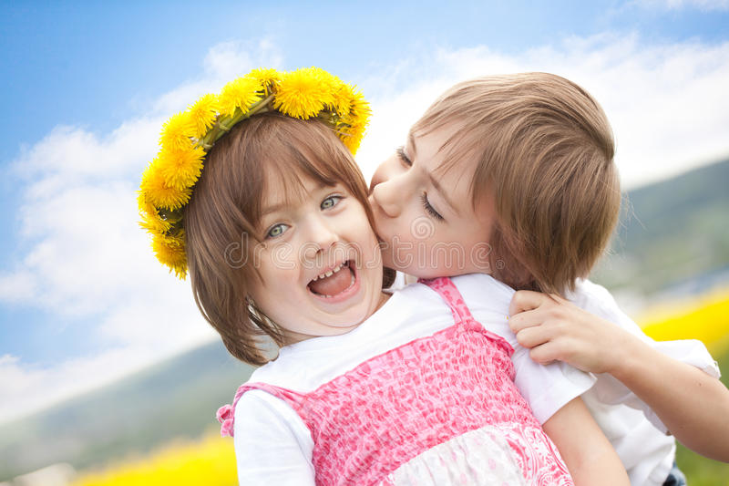 Cute young children kissing. Young boy kissing cute preschool sister with yellow daisy flower crown, blue sky and cloudscape background royalty free stock photos