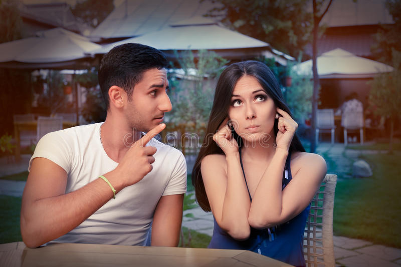 Cute Young Couple Arguing. Young adult couple arguing with funny expressions and gestures, out on a date royalty free stock images