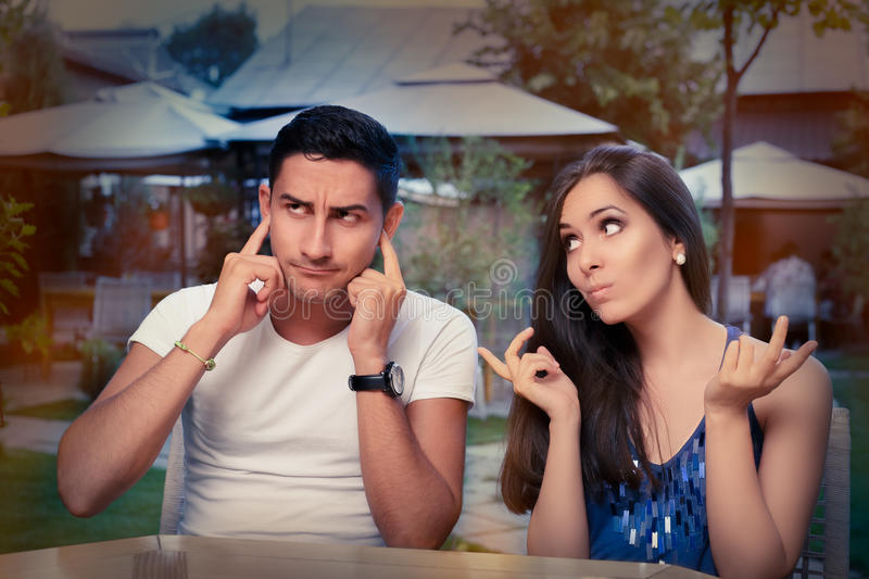Cute Young Couple Arguing. Young adult couple arguing with funny expressions and gestures, out on a date stock photography