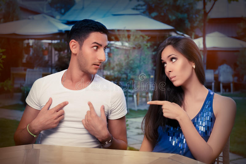 Cute Young Couple Arguing. Young adult couple arguing with funny expressions and gestures, out on a date royalty free stock image