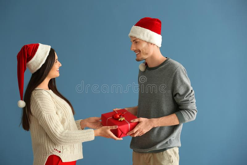 Cute young couple with Christmas gift on color background royalty free stock photo
