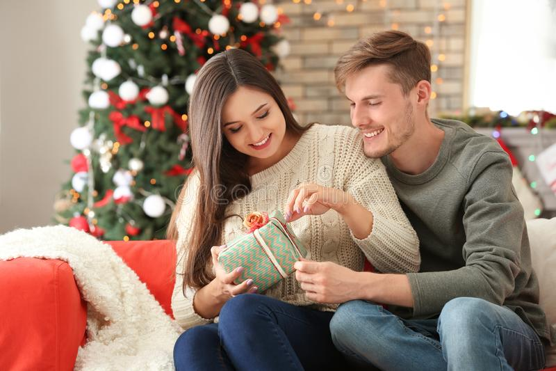 Cute young couple with Christmas gift at home royalty free stock photo