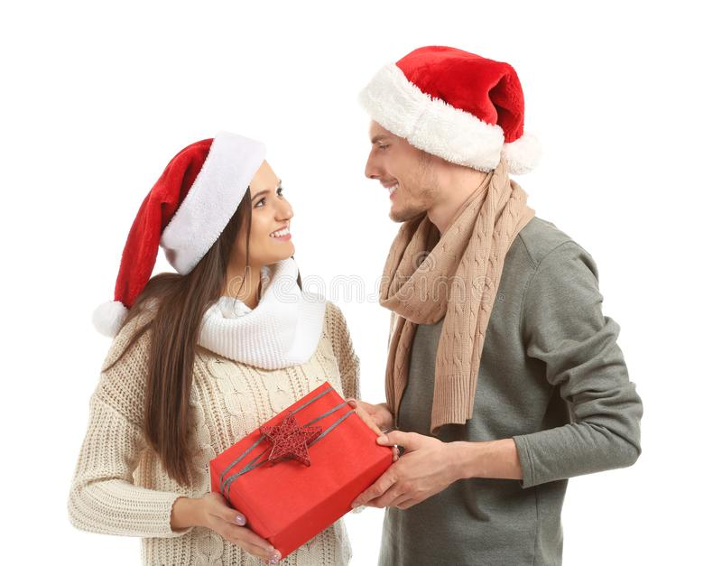 Cute young couple with Christmas gift on white background royalty free stock photos