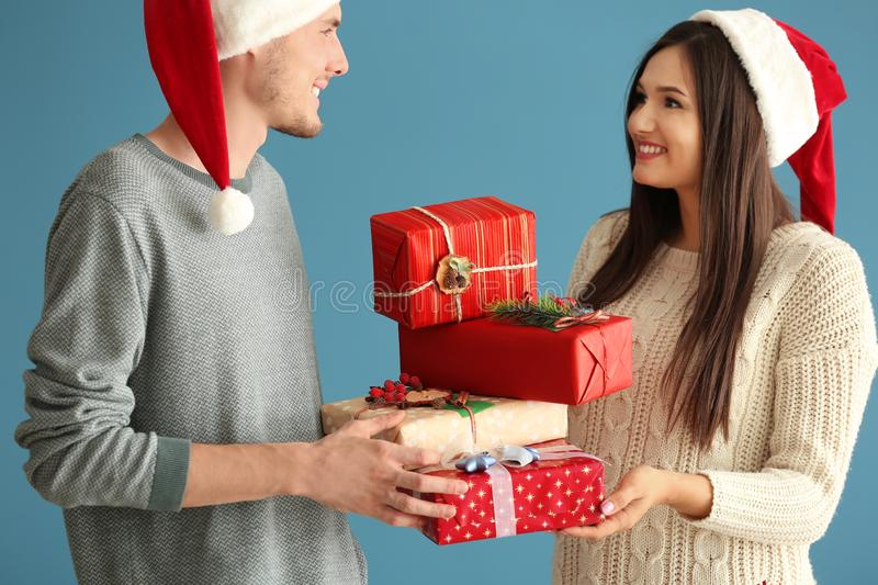 Cute young couple with Christmas gifts on color background royalty free stock images