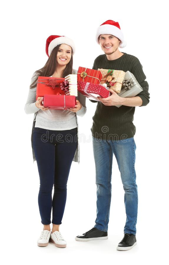 Cute young couple with Christmas gifts on white background royalty free stock photo