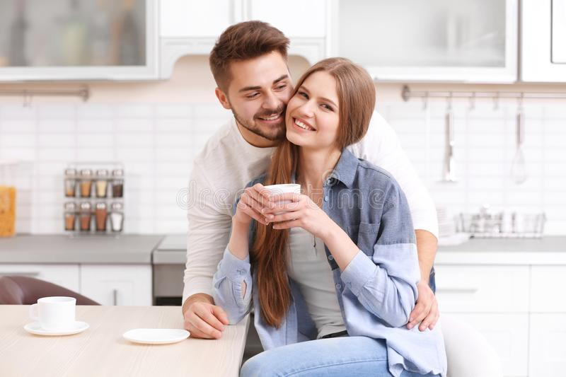 Cute young couple drinking coffee. In kitchen royalty free stock photos
