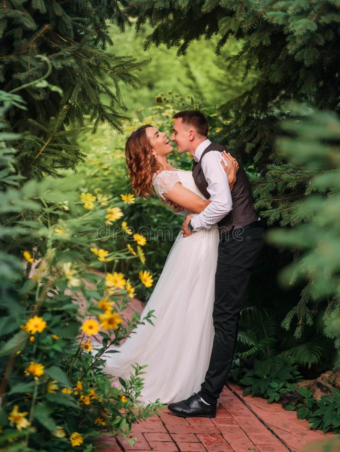 Cute young couple of the groom and the bride in a long white wedding dress are playing and laughing in a magnificent stock photo