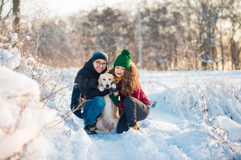Young couple portrait with dog in winter stock photography