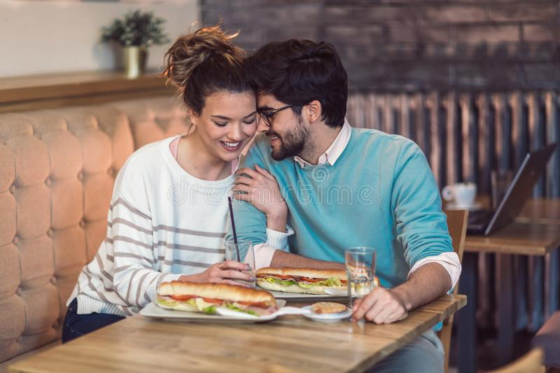 Cute young couple having a good time together in cafe royalty free stock photos