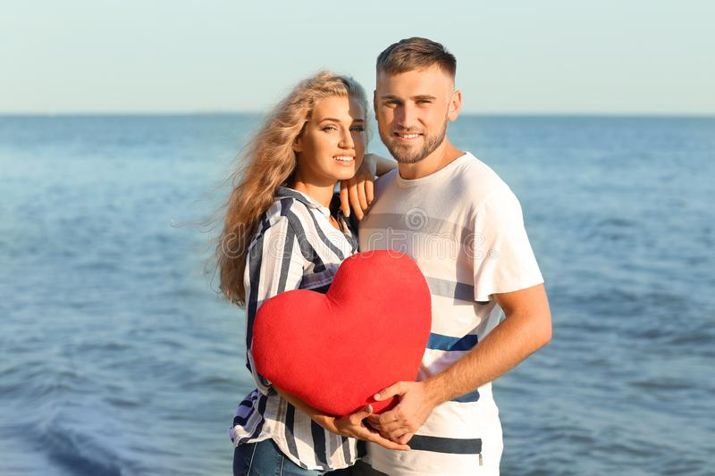 Cute young couple holding red heart on sea shore royalty free stock photography