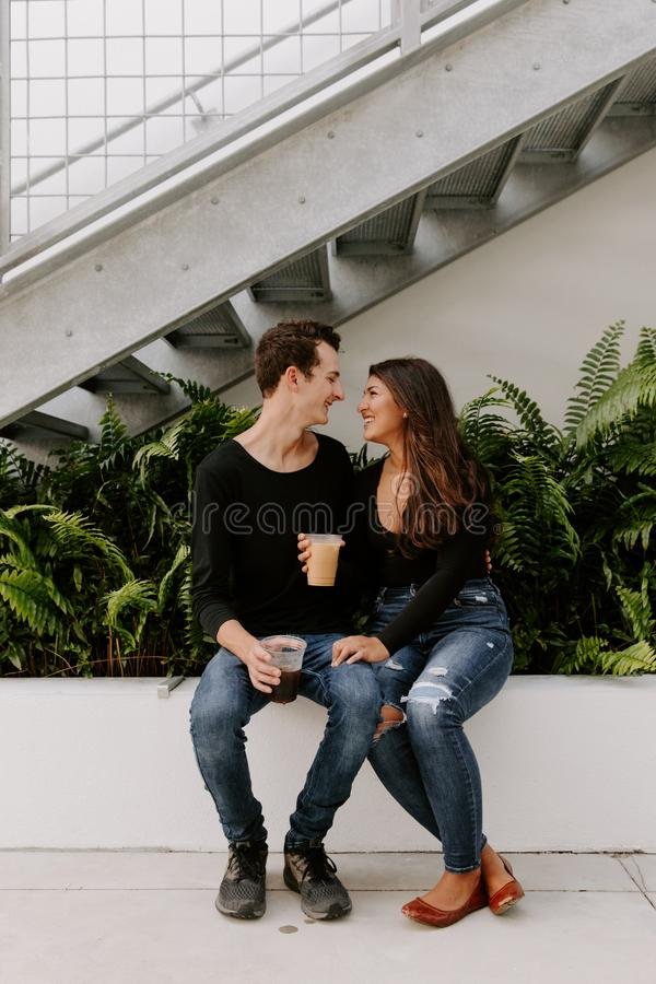 Cute Young Couple in Love Sitting in Front of Urban Concrete Stairs and Green Plants Cuddling, Kissing, and Holding their Cold Br stock foto's