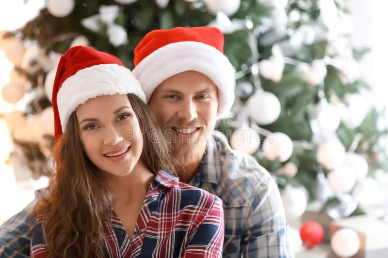 Cute young couple in Santa hats celebrating Christmas at home royalty free stock image