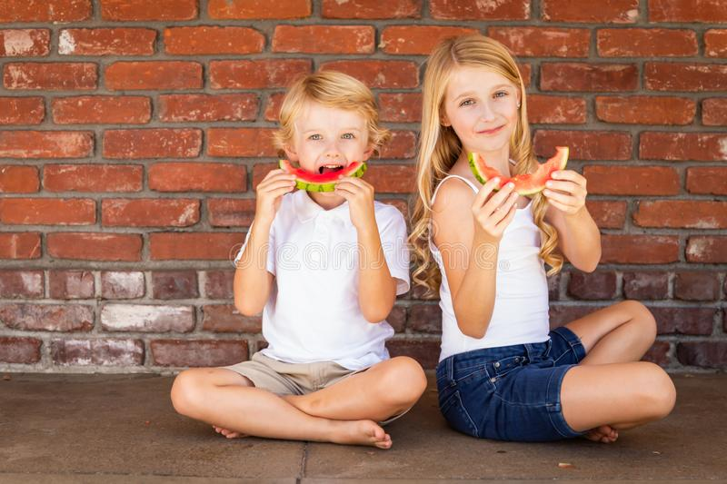 Cute Young Caucasian Boy and Girl Eating Watermelon Together royalty free stock photography