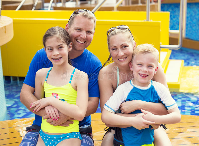 Cute young family on a cruise vacation together. Smiling cute young family enjoying a day at the pool while on a tropical cruise vacation together. Happy and stock photography