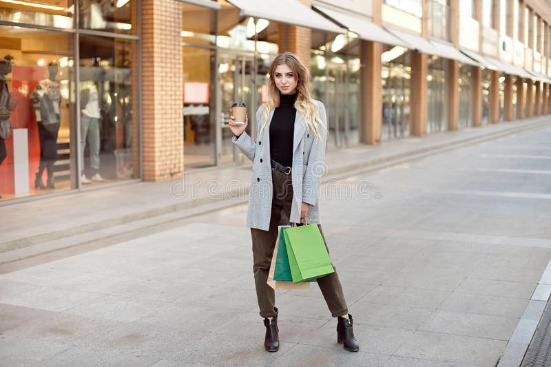 Cute young fashion woman with shopping bags standing near storefront shop windows on the street outdoors.  stock photos