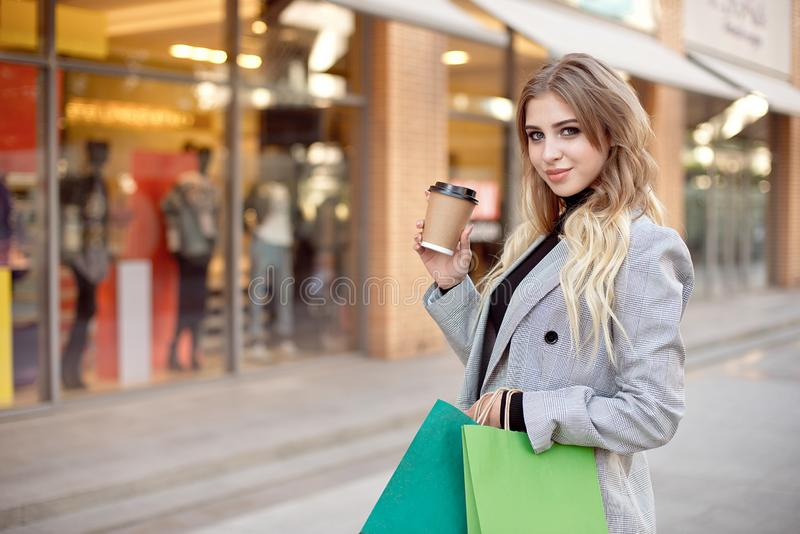 Cute young fashion woman with shopping bags standing near storefront shop windows on the street outdoors.  royalty free stock photos