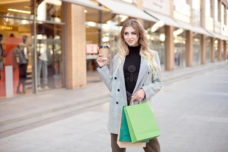 Cute young fashion woman with shopping bags standing near storefront shop windows on the street outdoors royalty free stock image