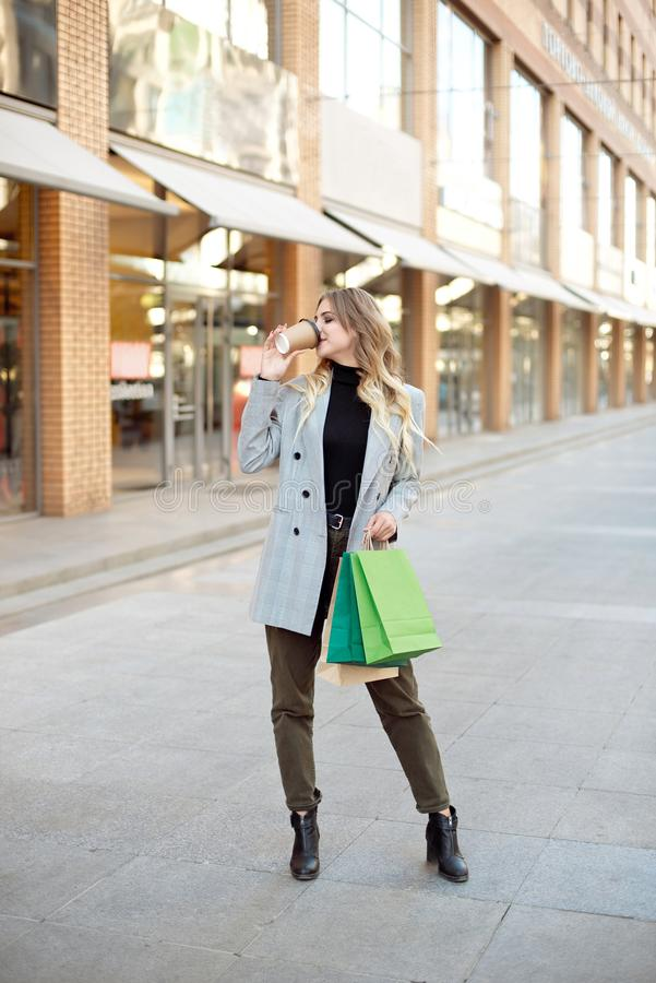 Cute young fashion woman with shopping bags standing near storefront shop windows on the street outdoors.  royalty free stock photo
