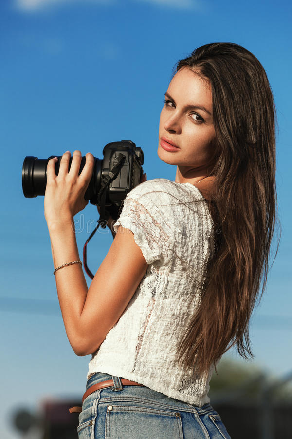 Cute young female photographer with camera outdoors. At the park royalty free stock photography