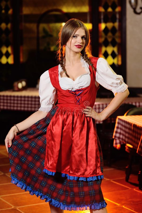 Girl in bavarian clothes in Oktoberfest on pub background. Cute young girl in bavarian clothes in Oktoberfest on pub background royalty free stock images