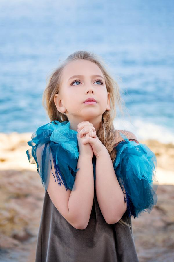 Cute young girl blonde praying asks for a dream come true folded hands in fists in a begging pose on the sea stock images