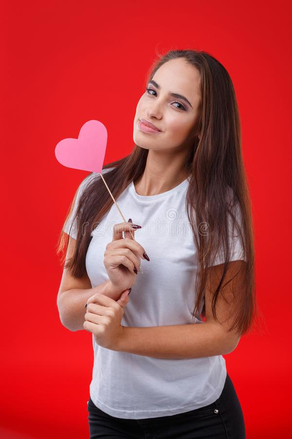 A cute girl, posing while standing and holding a small pink paper heart on a stick. Red background. royalty free stock photos