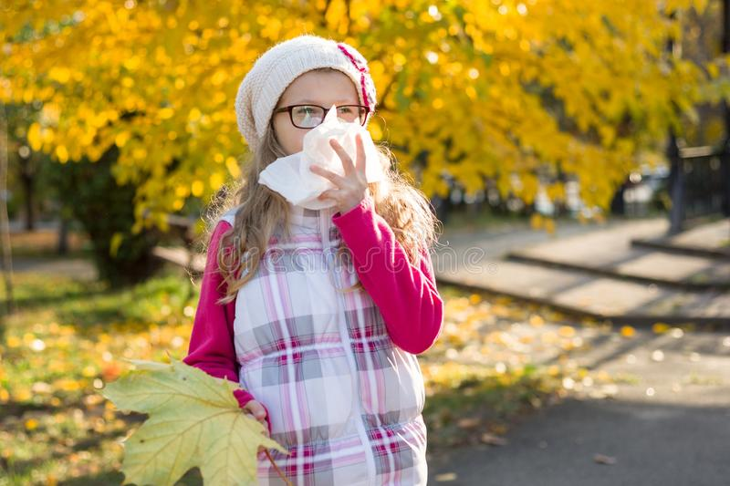 Cute young girl child in glasses sneezing in a tissue blowing his runny nose. Autumn - flu season. Cute young girl child in glasses sneezing in a tissue blowing stock image