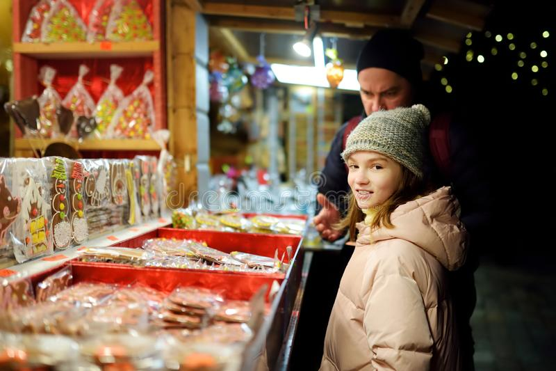 Cute young girl choosing sweets on traditional Christmas market in Riga, Latvia. Kid buying candy and cookies on Xmas stock photography